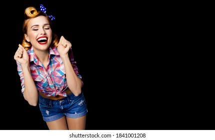 Unbelievable news! Excited surprised, very happy pinup woman. Pin up bond girl with open mouth and closed eyes with raised hands. Retro and vintage concept. Black background. Copy space blank area.