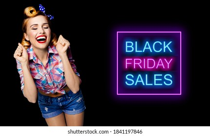 Unbelievable news! Excited surprised, very happy pinup woman. Pin up bond girl with open mouth and closed eyes with raised hands. Retro and vintage concept. Dark background. Black Friday sales ad sign