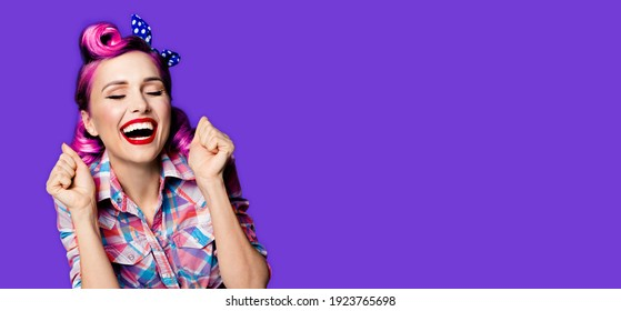 Unbelievable news! Excited surprised, very happy purple woman. Pin up girl with open mouth and closed eyes with raised hands. Retro and vintage concept. Violet color background. Wide composition image
