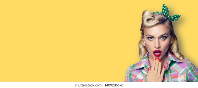 Unbelievable news! Excited surprised woman. Pin up girl keeping hand near open mouth. Retro fashion and vintage concept. Yellow color background. Copy space for some advertise slogan or sign text.