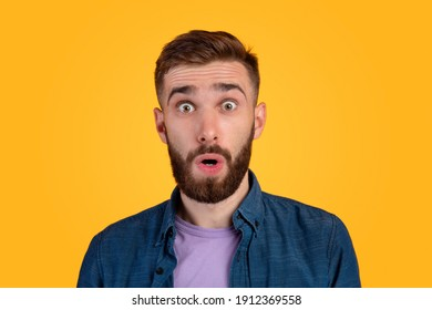 Unbelievable news. Portrait of bearded young guy opening his mouth and eyes in shock, looking at camera on orange studio background. Thunderstruck millennial man feeling astonished