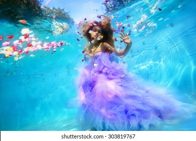 Unbelievable underwater beauty blond girl in fabulous dress, surrounded by petals of roses. Real shot
