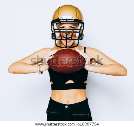 e762f02034841 Unbelievably beautiful athletic blonde girl in helmet on head posing in black  outfit and holding ball