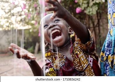 Unglaublich glückliches afrikanisches Kleinkind, das von seinem Dach in seinem Haus in Bamako, Mali, die Regentropfen genießt.