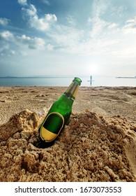 Unbranded Beer bottle on a sandy beach.