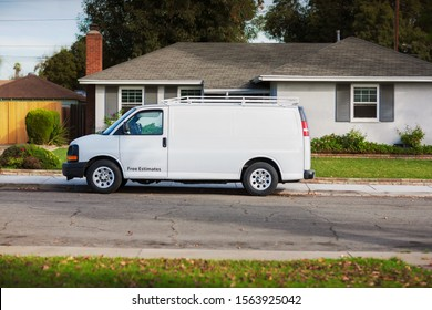 An unbranded home service van parked in front of a house for repairs or handyman work.