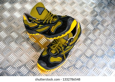 Unbranded modern sneaker in the gym. Black-Yellow. Comfortable shoes. Wearing sport shoes, doing wide step, demonstrating healthy way of life, wide shot. copy space for text.