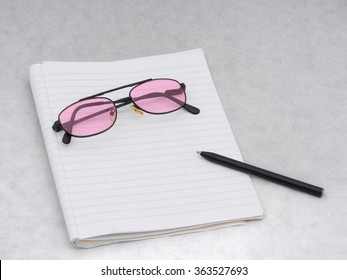 Unbranded reading glasses with pink colour lenses on writing book with pen.  Dyslexia, visual stress. Or just rose tinted optimism!