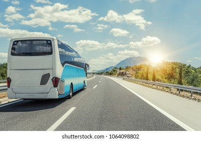 Unbranded tourist bus rushes along the asphalt high-speed highway.