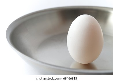 Unbroken egg in a frying pan on a white background