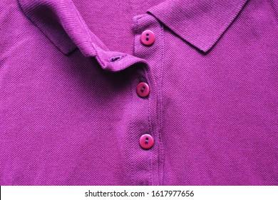 Unbuttoned violet polo shirt, casual clothes close up. Vivid colorful purple color t-shirt, plain vivid violet colour fabric, cotton polo shirt for men and women top view