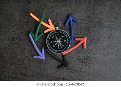 Uncertain alternative path or multiple life direction concept, compass at the center with magnet arrows pointing random multi directions on dark black chalkboard cement wall.