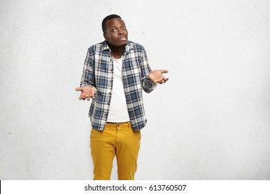 Uncertain confused young African American male shrugging shoulders and gesturing in uncertainty while failing to explain himself. Clueless dazed dark-skinned man having unsure doubftul look