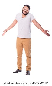 Uncertain latino man with beard. Wears beige pants and grey t-shirt. Full length portrait. Isolated on white background.