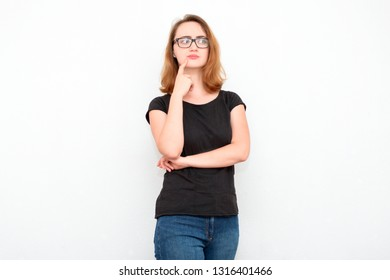 Uncertain red-haired woman in black glasses is standing on a light background, doubt, decision making, thinking.