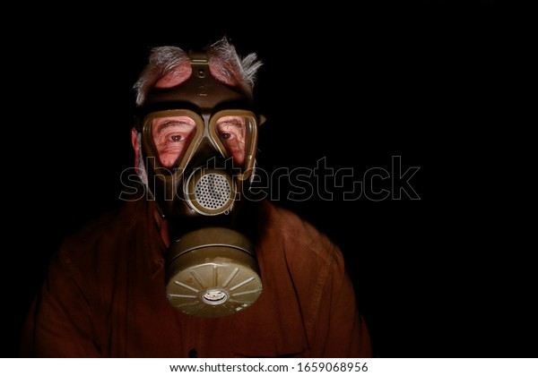 Uncertain times. Fearing the coronavirus, an older man has put on his old gas mask to protect himself.