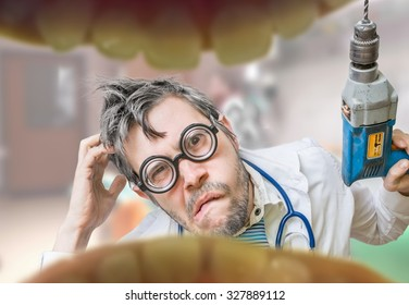 Uncertain and unsure crazy dentist doctor looks into mouth and wants to drill tooth decay.