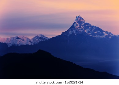 Unclimbable Nepalese mountain peak of Machapuchare fishtail in a warm glow morning sunrise. A mountain in the Annapurna Himalayas of north central Nepal. View from Australian Base Camp, Pokhara, Nepal