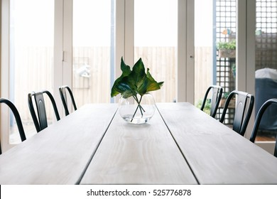 Uncluttered light bright contemporary dining room table with glass doors background