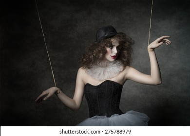 uncombed sensual woman with gothic puppet costume, uncombed hair and clown make-up. She wearing vintage tutu and bowler