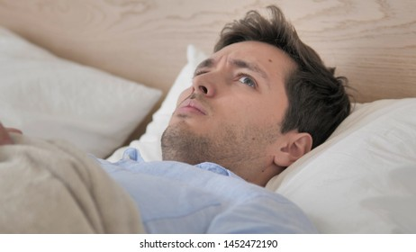 Uncomfortable Man Waking up from Sleep in Bed