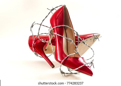 Uncomfortable shoes, sexism in fashion and foot pain concept with high heel stilettos wrapped in barbed wire representing the aches and pains caused to your feet by poorly constructed footwear
