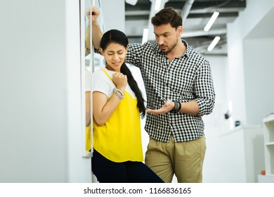 Uncomfortable talk. Scared young girl feeling uncomfortable and closing her eyes while a tall young man leaning to her and telling unpleasant words