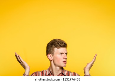 uncomprehending bewildered puzzled perplexed confused man pointing upwards with hands. portrait of a young guy on yellow background pop up or peek out from the bottom. free space for advertisement.