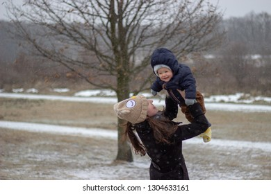 unconditional innocent love between smiling loving mother and adorable smiling baby son in winter with snowy landscape in the background