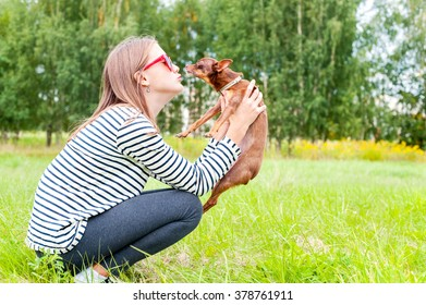 Unconditional love. Teenage girl sitting on grass in summer green park and  kissing her little brown toy-terrier dog. Multicolored outdoors horizontal image.