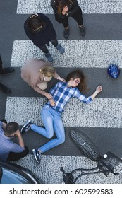 Unconscious biker lying on the road surrounded by pedestrians after car crash