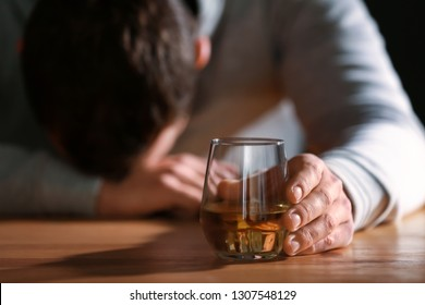 Unconscious drunk man with glass of whiskey at table