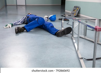 Unconscious Handyman Fallen From Ladder With Equipments Lying On Floor