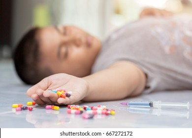unconscious male child laying down on floor with tablets beside him