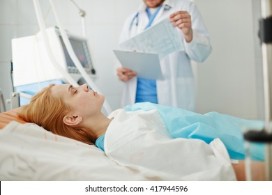 Unconscious woman lying on bed in hospital with doctor standing nearby