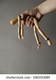 Unconscious wooden dummy with abandoned limbs grabbed by a hand. Gray Background. Vertical photo. Room for text