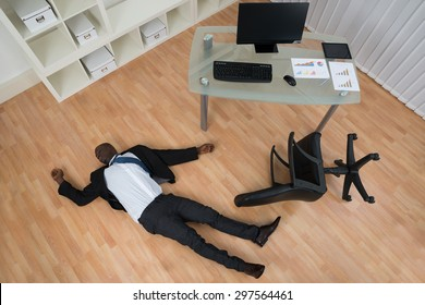 Unconscious Young African Businessman Lying On Floor In Office