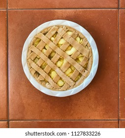 Uncooked apple pie with latticework in a round dish