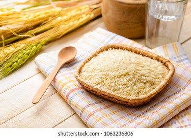 Uncooked basmati rice, extra long type, in a little plate on a towel put on a wooden table. Basmati rice is a base ingredient for many Asian Oriental recipes.