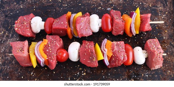 Uncooked beef kebabs with vegetables and spices on brown background