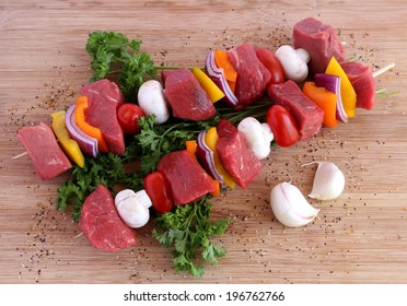 Uncooked beef kebabs with vegetables and spices on wooden board
