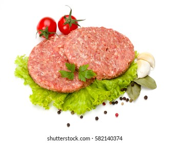 Uncooked beef and pork hamburger meat on lettuce