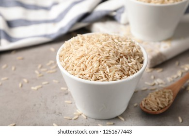 Uncooked brown rice in small bowl on table. Space for text