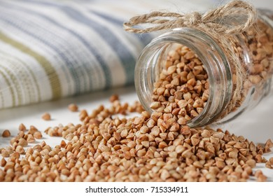 Uncooked buckwheat scattered from glass jar on the kitchen table. Selective focus