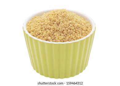 Uncooked bulgur wheat in a bowl on a white background