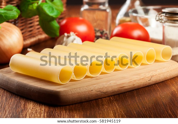 Uncooked cannelloni pasta on cutting board and ingredients. Italian cuisine