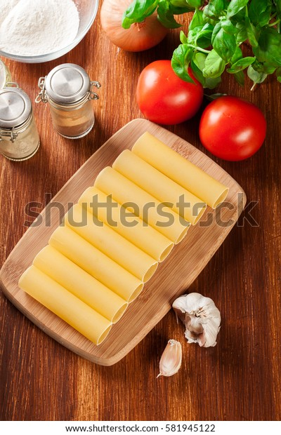 Uncooked cannelloni pasta on cutting board and ingredients. Italian cuisine. Top view