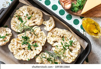 Uncooked cauliflower slices with cheese, garlic, herbs, and spices in a baking sheet. Top view. Cooking baked cauliflower steaks. Tasty vegetarian food.