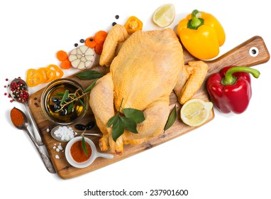 Uncooked chicken with spices and vegetables on a wooden cutting board, isolated over a white background, top view