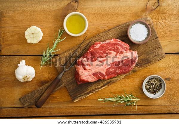 Uncooked chuck eye steak on wooden board on wood